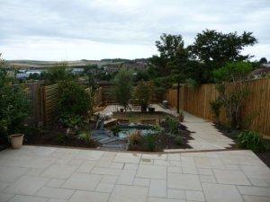 Full garden makeover including paving, ornamental pond, specimen planting, screen and steps