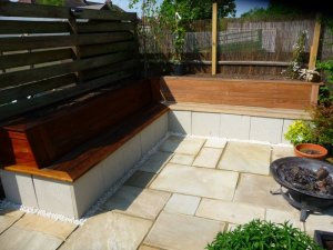 Ipe decking boards used to create a seating area with raised beds and Indian sandstone paving
