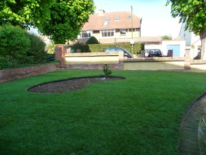 Freshly laid turf gives a new lease of life to this front garden with feature planting area