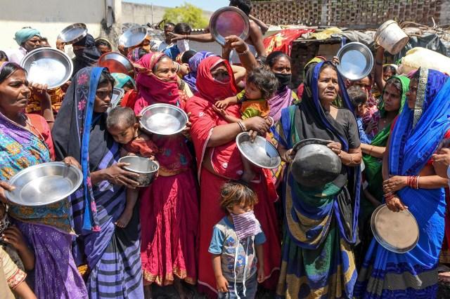 Trabajadores migrantes y familias de los estados de Bihar y Uttar Pradesh sostienen utensilios de cocina mientras protestan contra el gobierno por la falta de alimentos en un área de tugurios en Amritsar el 22 de abril de 2020 (Foto de NARINDER NANU / AFP)