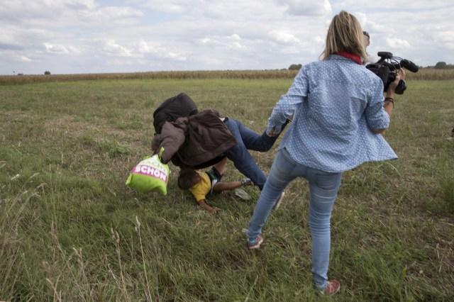 Un migrante que lleva un niño se cae después de que la camarógrafa de televisión (R) Petra Laszlo le pega una patada mientras intentaba escapar de un punto de recolección en la aldea de Roszke, Hungría, el 8 de septiembre de 2015 (REUTERS/Marko Djurica)