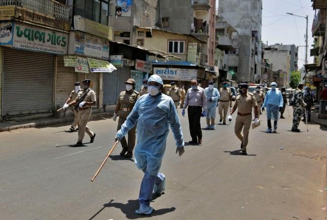 Policías indios patrullan una calle durante la cuarentena en Ahmedabad, India, el domingo 19 de abril de 2020. La India es uno de los lugares más concurridos de la Tierra, una nación donde el distanciamiento social es imposible para millones de personas (Foto AP/Ajit Solanki)