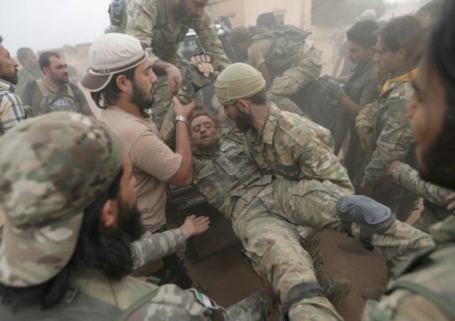 Combatientes rebeldes sirios asisten a su compañero herido cerca de la ciudad fronteriza de Tal Abyad, Siria, el 24 de octubre de 2019 (REUTERS/Khalil Ashawi)