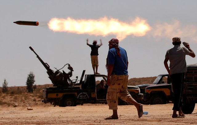 Combatientes contrarios a Muammar Gaddafi disparan un lanzacohetes múltiple cerca de Sirte, uno de sus últimos bastiones en Libia, el 24 de septiembre de 2011 (REUTERS/Goran Tomasevic)