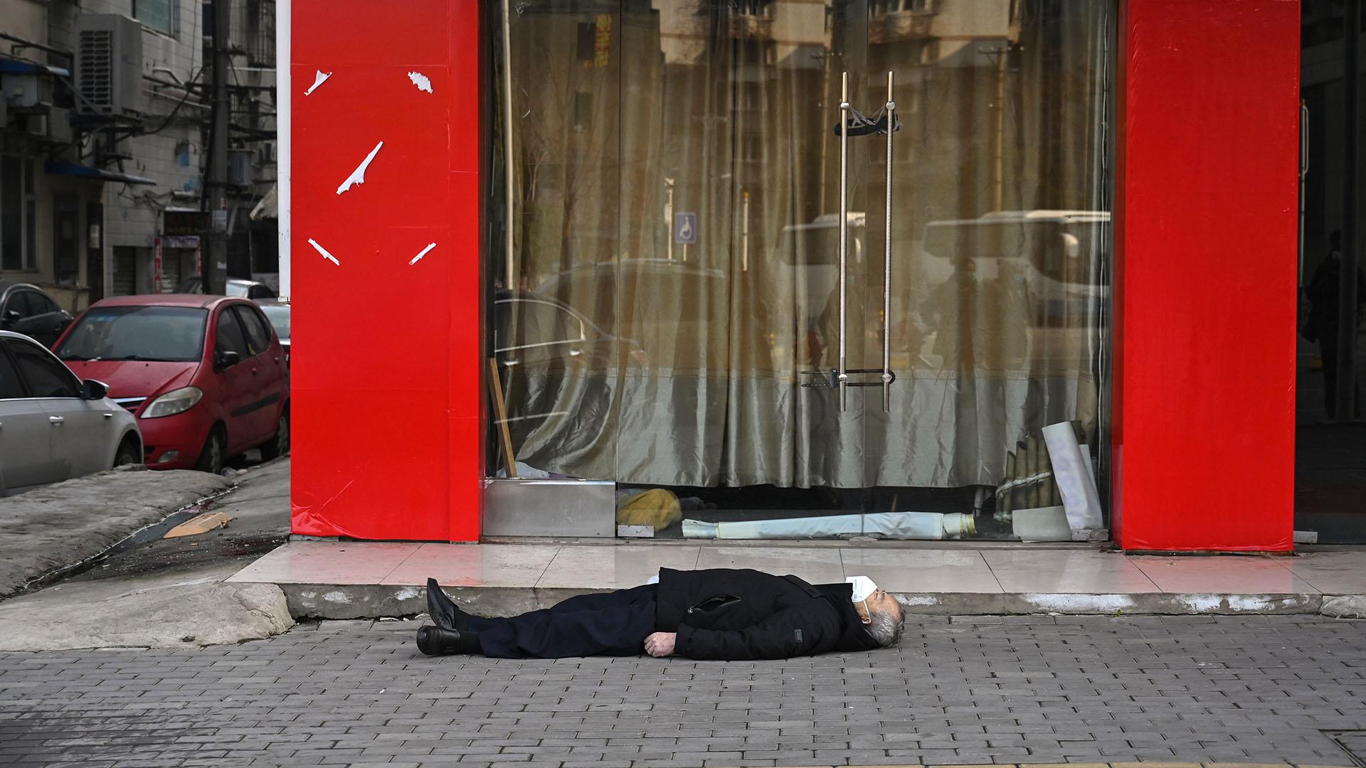 El cuerpo de un anciano sin vida en plena calle (Héctor RETAMAL / AFP)