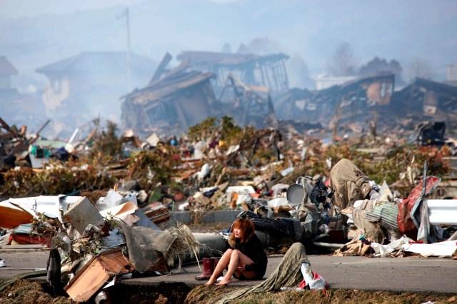Una mujer llora sentada en una carretera después de que un terremoto y un tusnami destruyó la ciudad de Natori, Prefectura de Miyagi, en el norte de Japón, el 13 de marzo de 2011 (REUTERS/Asahi Shimbun)
