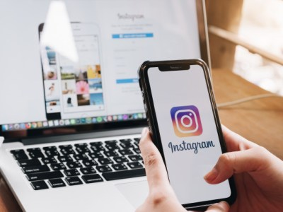 mujer sostiene un smartphone con instagram de fondo