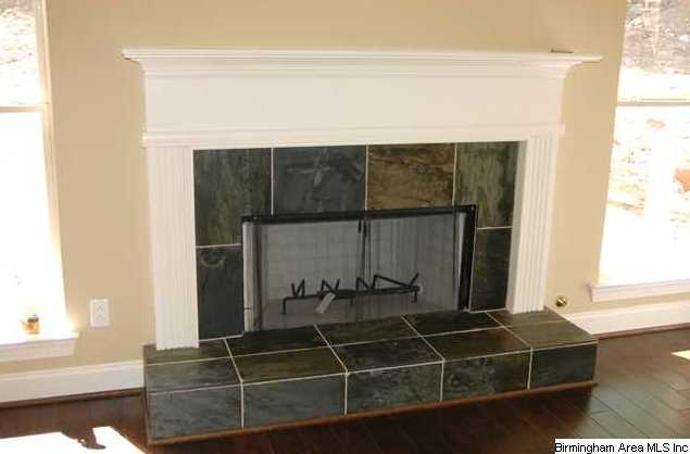 The beautiful woodburning fireplace has gas starter and