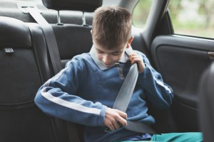boy bulking himself in with a seatbelt