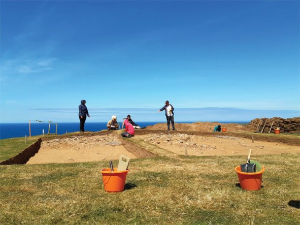 Five archaeologists next to two trenches, excavating a Bronze Age burial mound at Berk Farm as part of the Round Mounds of the Isle of Man project.