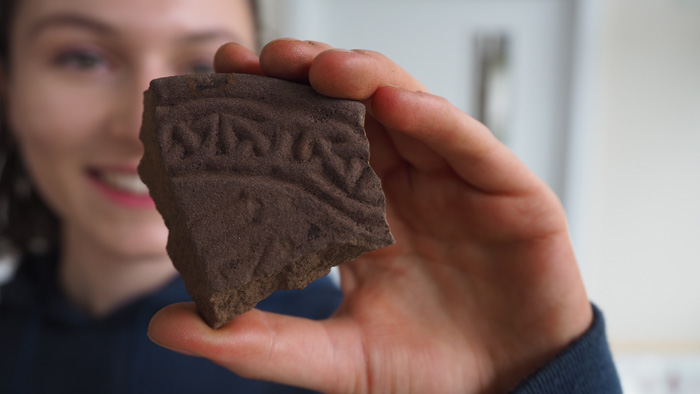 A fragment of a namestone inscribed with intricate knotwork.