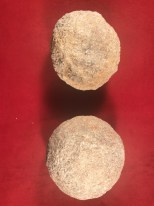 Two stone ballista balls on a red background