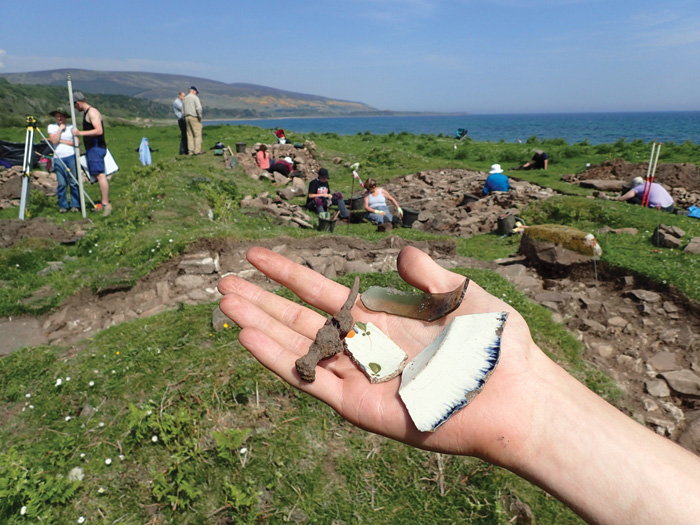 A hand holding finds including a nail, pottery, and glass, in front of the excavation