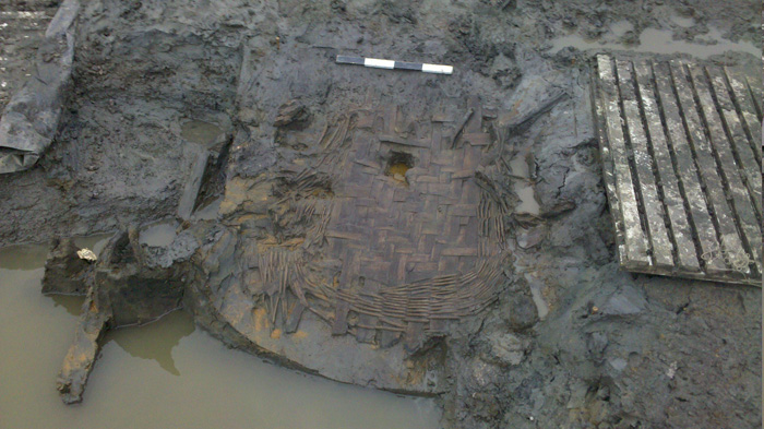 A basketry tray preserved by the waterlogged condition of the pit it was found in, still partially under water