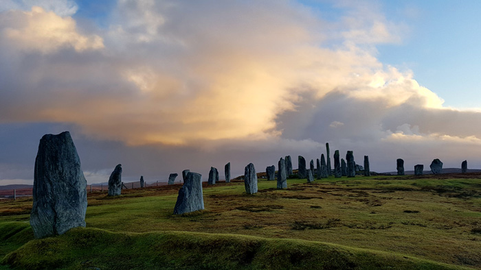 The Callanish Stones with a cloudy sunset behind them