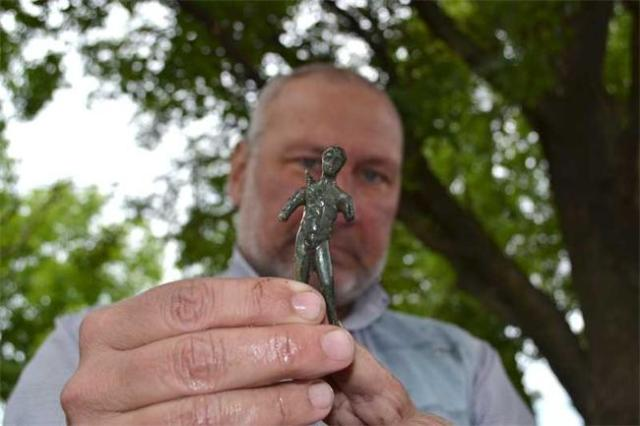 Bulgarian archaeologist Prof. Nikolay Ovcharov shows the 3rd century AD bronze statuette of Greek god Apollo with a bow carrying a bow over his shoulder discovered in the first 2 days of the 2015 summer excavations of the prehistoric, ancient, and medieval rock city of Perperikon in Southern Bulgaria. Photo: 24 Chasa daily