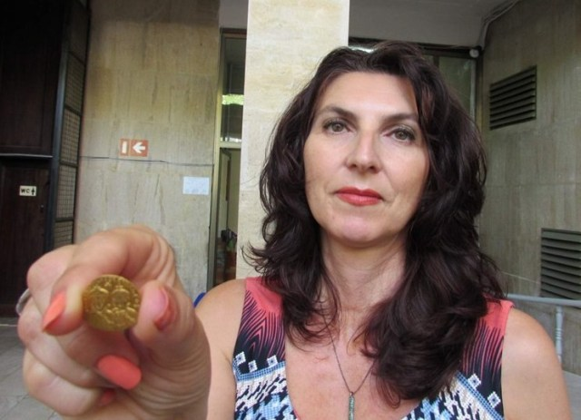 Numismatist Zhenya Zhekova from the Shumen Regional Museum of History in Northeast Bulgaria shows the 8th century AD gold coin of Byzantine Emperor Constantine V Copronymus which was found by a shepherd near the early medieval Bulgarian capital Pliska. Photo: Tsvetelina Georgieva, Trud daily