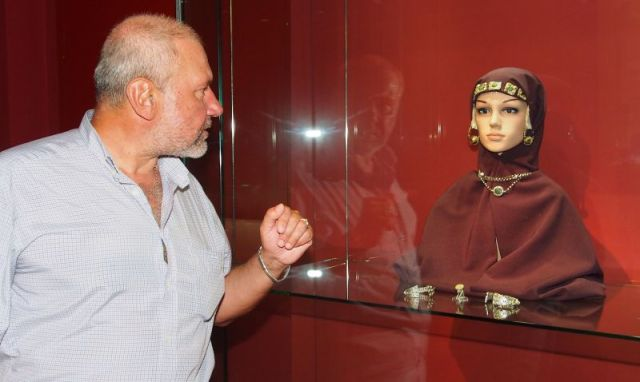 Archaeologist Nikolay Ovcharov looking at the jewels worn by a noblewoman from the time of the medieval Bulgarian Empire on display in the Varna Museum of Archaeology. The displayed jewels include earrings (ear tabs) like the ones recently discovered by a hunter near Dolishte, Varna District. Photo: BGNES