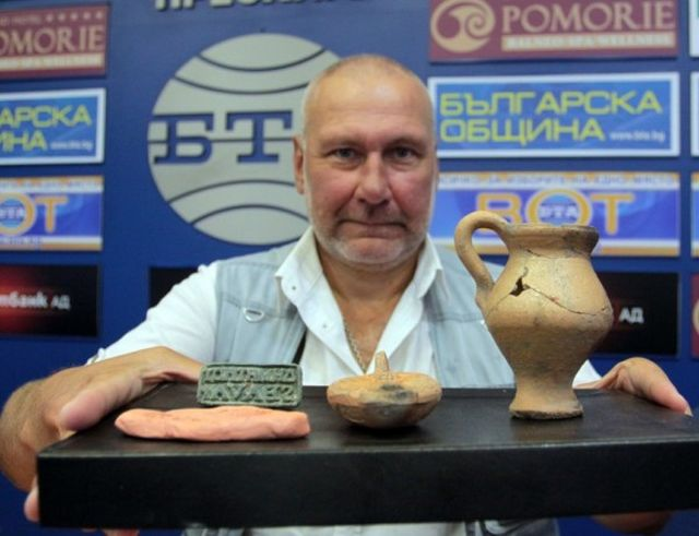 Archaeologist Prof. Nikolay Ovcharov posing with the Ancient Roman Era bronze seal, double wick clay lamp, and wine cup his team found at Perperikon recently. Photo: Standart daily