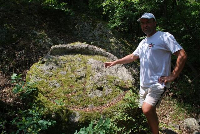 Lead archaeologist Zdravko Ivanov shows a large stone altar found outside the walls of the Late Roman and Early Byzantine fortress built on the Thracian shrine. Photo: Mineralni Bani Municipality