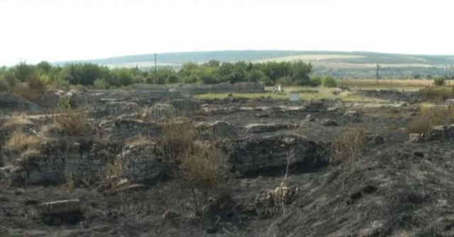 "The newly charred ruins of the once glorious Ancient Roman colony Ulpia Oescus near Gigen in Northern Bulgaria - the recent of an arson and the ""scorched earth policy"" apparently adopted by the brutal treasure hunters who have been looting the site. Photo: TV grab from BNT"