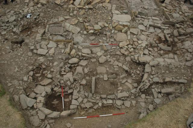 A complex arrangement of walls, hearth, internal fixtures built over Structure A
