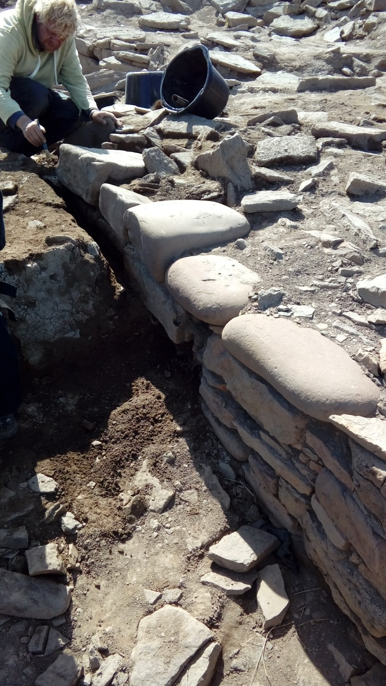 Marc revealing more of the boulder topped wall in Area Q as the baulk gets excavated