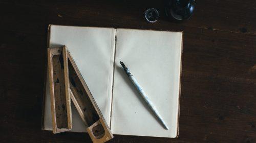 white fountain pen on white open book
