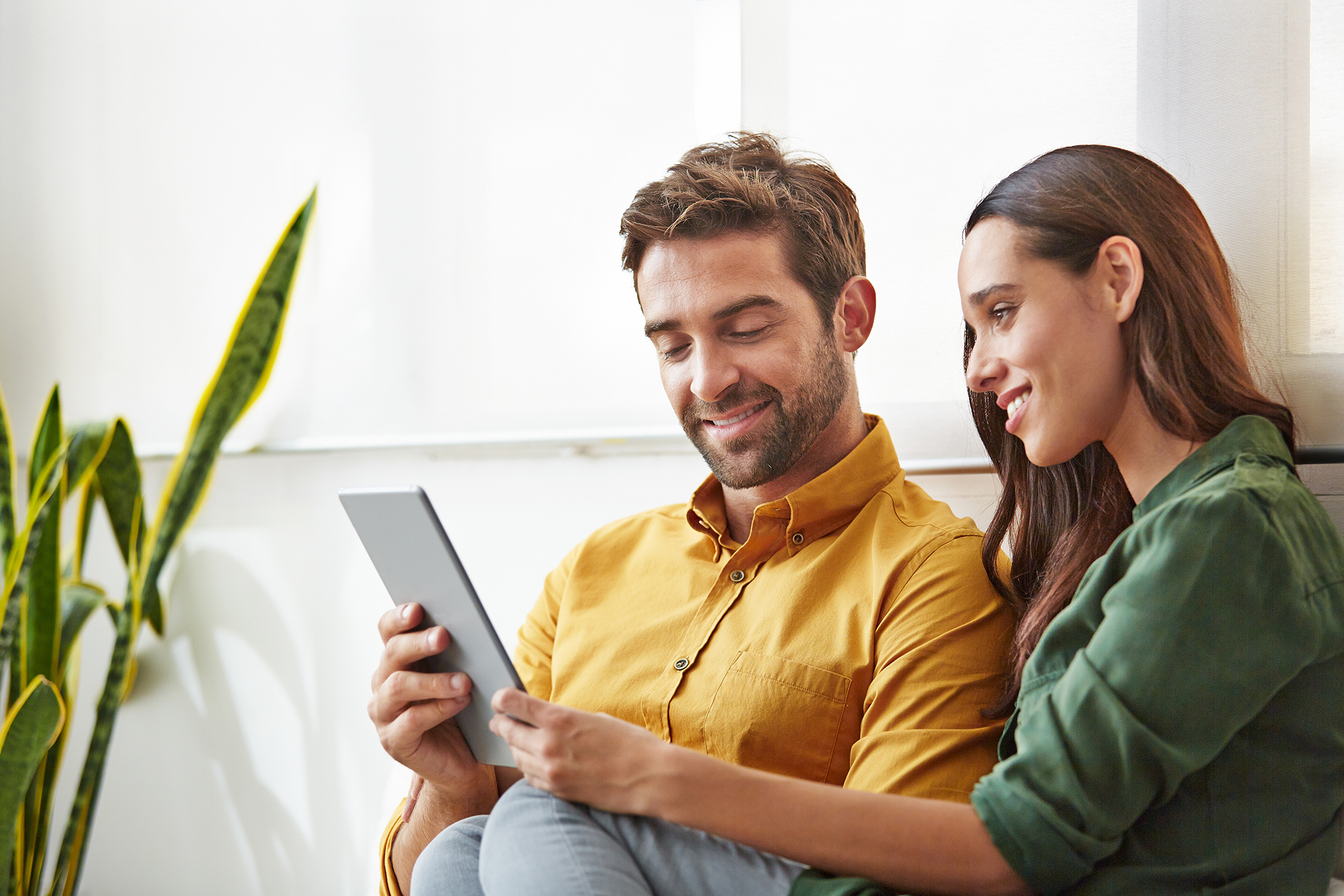 Couple reading the Infertility Solutions magazine on a tablet