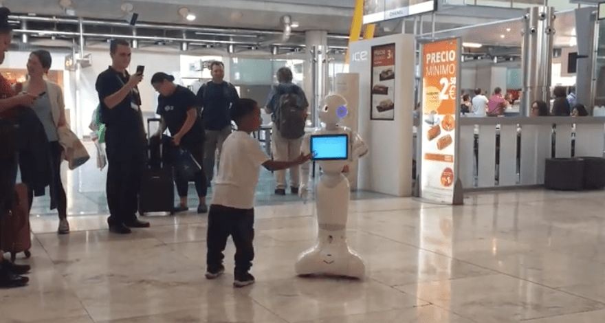 A boy dances with a robot