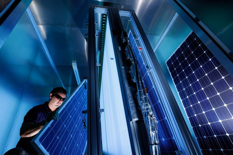 A testing company works with solar panels while testing the cybersecurity of solar inverters.