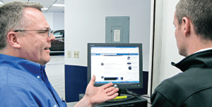 Photo by BARBARA KOLB Employees at Acura of Brookfield discuss a Facebook post. The dealership does not ban its employees from social media sites, but it monitors useage and talks with staff who abuse the privilege.