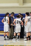 Coach Marc Heidorf huddles with the team who looks at the next designed play stategy.