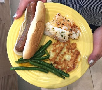 The Wisconsin tailgating dish includes a brat, cod, potato pancakes and green beans.