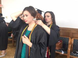 Sophie Beck, Brittany Seemuth prepare for the graduation ceremony.