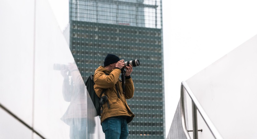 Photographer taking a picture of a building - How to Start with Architecture Photography?