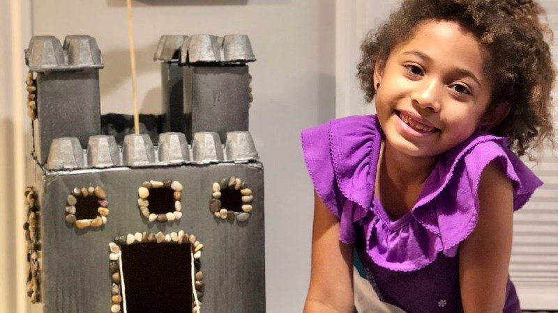 A girl in purple posing next to a silver fort architectural model that she created during a virtual workshop