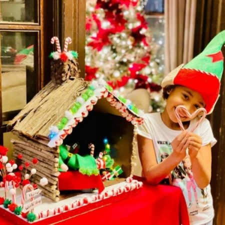 Girl wearing holiday elf hat posing with candy canes in front of a log cabin elf home project