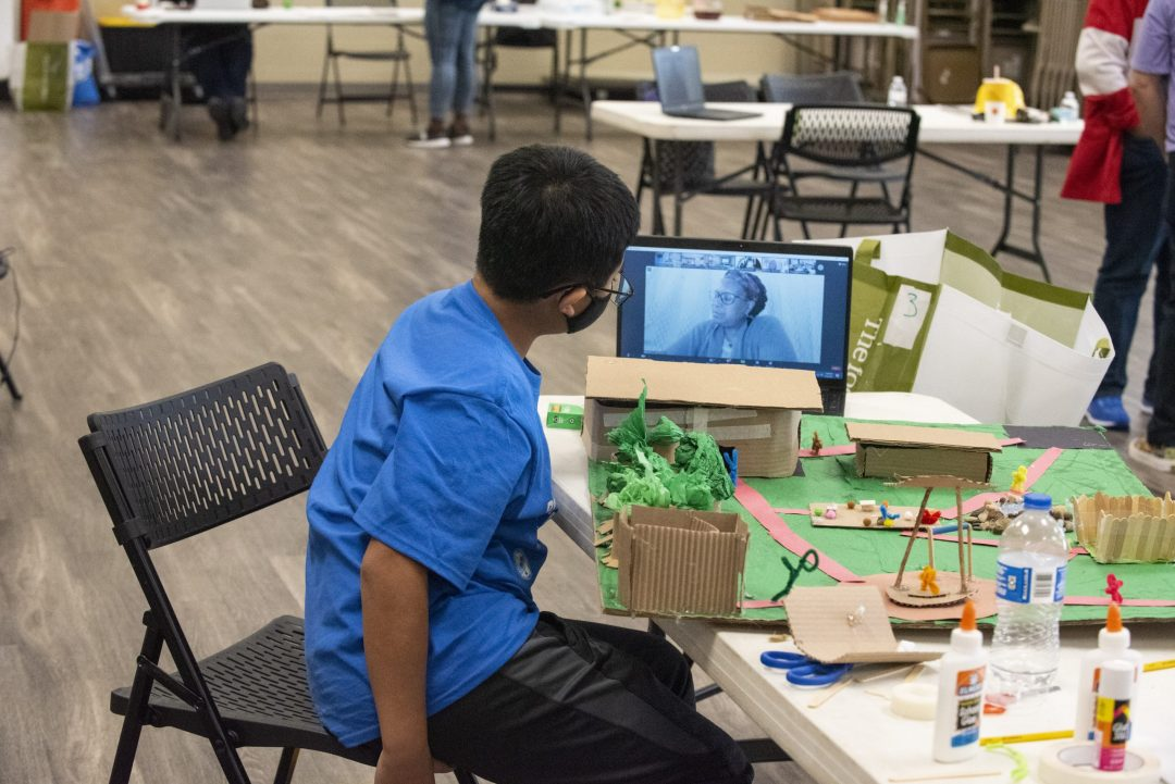 A teenage boy with brown hair in a blue tshirt leaning in towards a laptop screen displaying ArchForKids founder Janny Gedeon to listen to her virtual feedback on his vacant lot transformation project