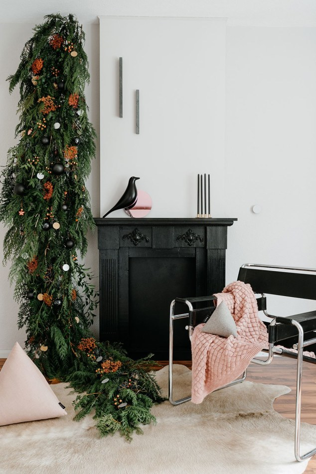 living room with hanging evergreen tree with orange flowers and shiny ornaments