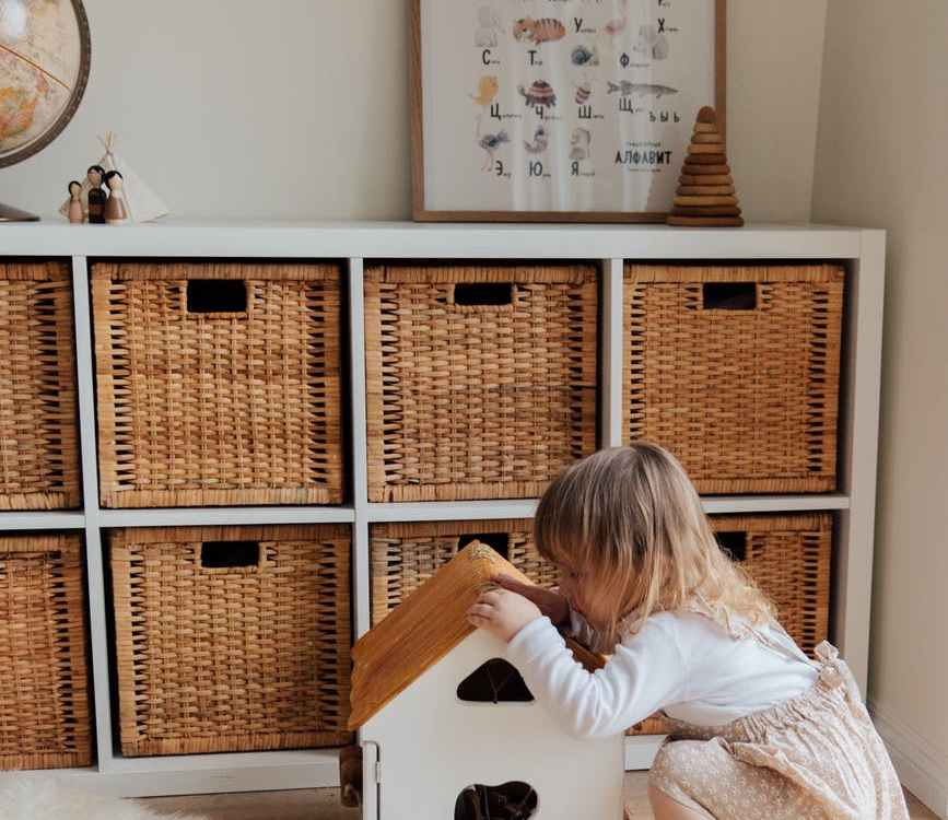 girl playing with a wooden toy house