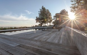 Sunset view of rectangular black bottom pool and reclaimed wood decking