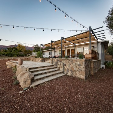 45 degree view of tiered back patio and steel trellis