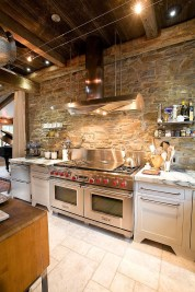 Industrial Kitchen With Stone Wall And Marble Countertops