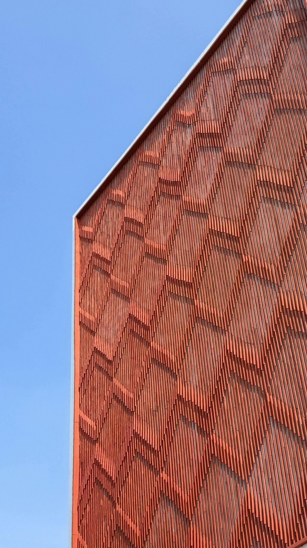 Clay roof tiles façade to minimize heat gain and has decorative function, at Vadodara, by Manoj Patel Design Studio 74