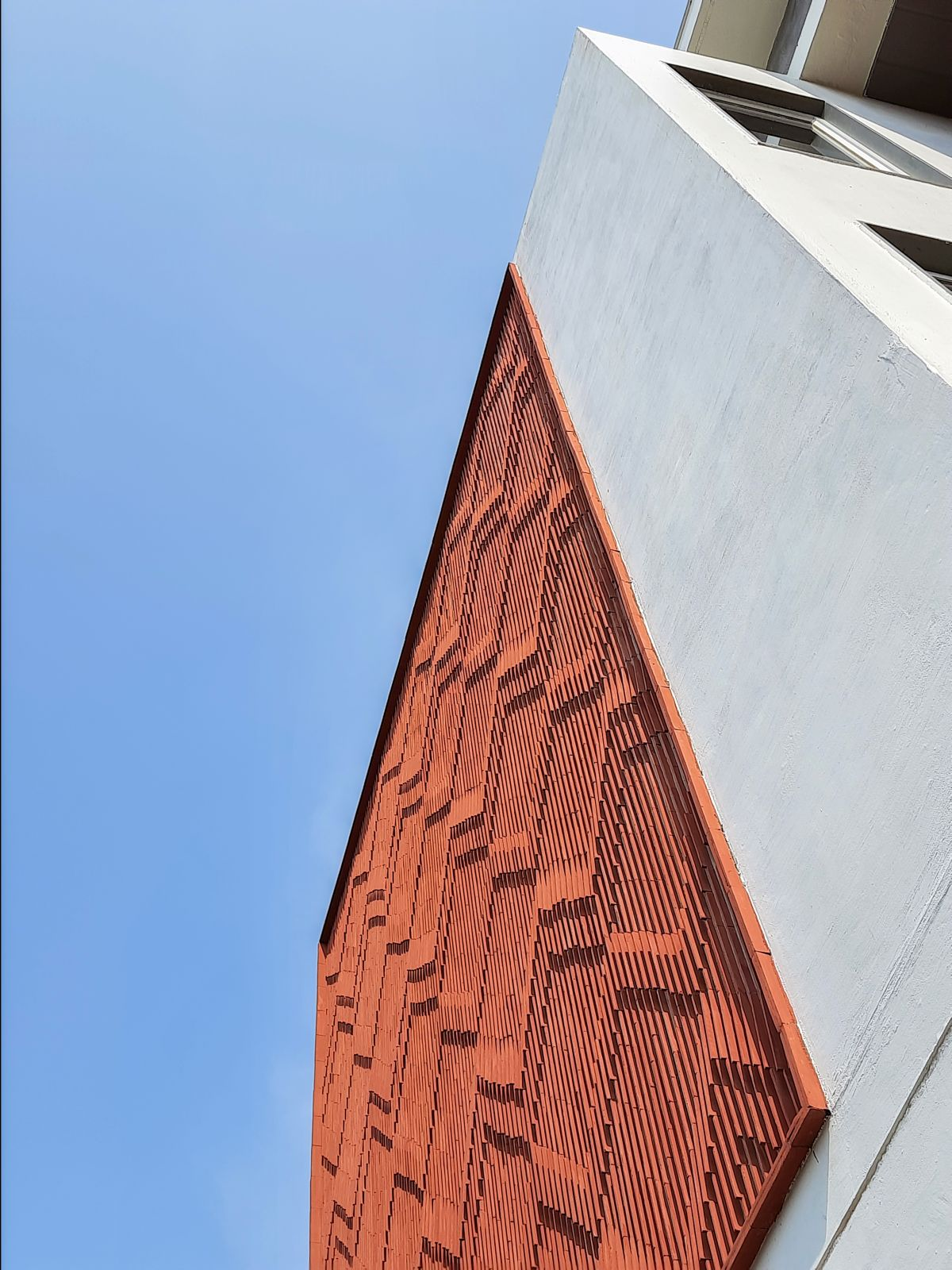 Clay roof tiles façade to minimize heat gain and has decorative function, at Vadodara, by Manoj Patel Design Studio 68