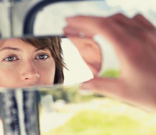 odbicie kobiety w lusterku samochodowym