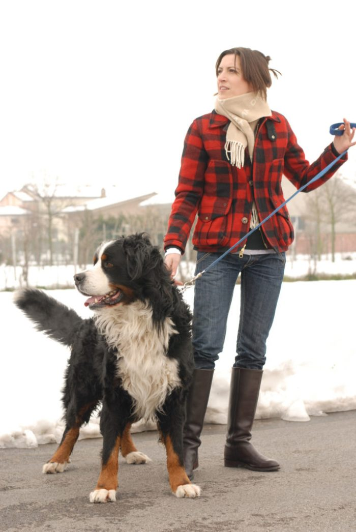 Woman wearing Filson jacket and holding a dog leash