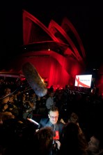 Bono talks to the media as the red sails of the Opera House loom