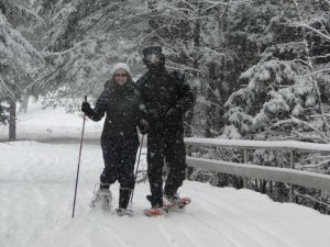 A snowshoeing couple enjoying fresh snowfall at Lapland Lake.
